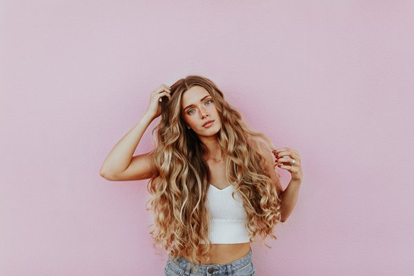 woman with a long blonde curly hair standing in front of a light pink colored bagckground