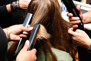 Brunette being styled using flat irons and comb