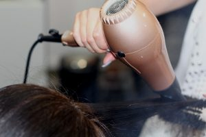 A hair dresser's hand holding a hair dryer while the other is holding a hair brush to shape hair