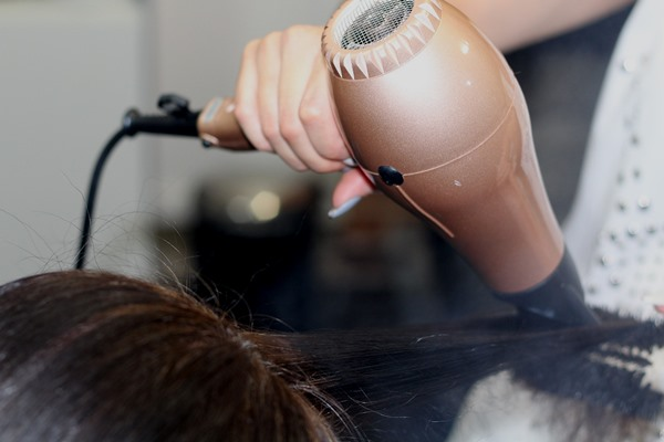 A hairdresser's hand holding a hair dryer while the other hand is holding a hair brush to shape hair