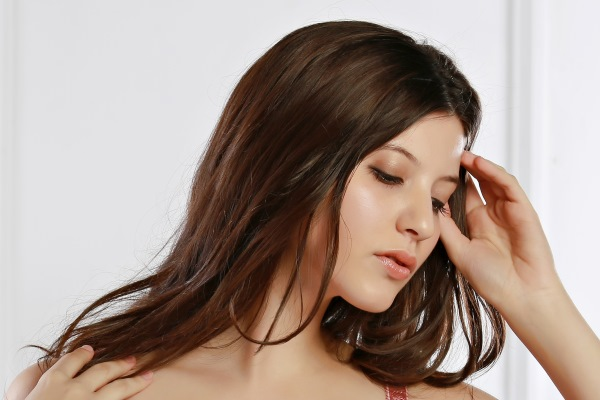 Brown-haired woman touching the ends of her hair