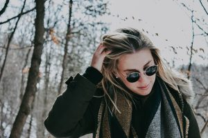 Woman in sunglasses touching her blonde hair