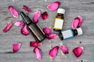 Bottles of essential oils with some rose petals
