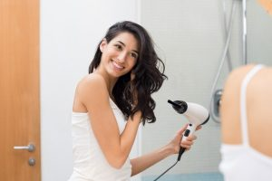 Pretty woman in white tank top using a blow dryer in front of the bathroom mirror