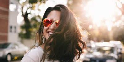 Woman in red sunglasses showing off healthy hair