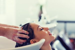 Woman having her hair shampooed by an assistant