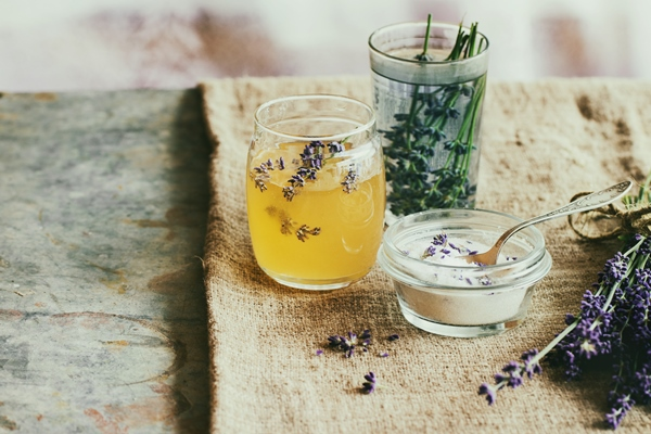 Argan oil in a glass jar with few lavender flowers