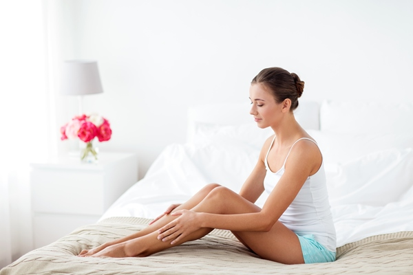 Girl in white tank top and shorts sitting on a bed with arms over her slightly bent legs