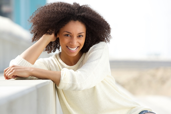 Beautiful African-American girl in white sweatshirt; she has thick kinky hair