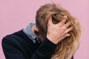 Man touching his hair in pink background
