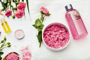 A bottle of rosewater, argan oil, and rose flowers on white surface