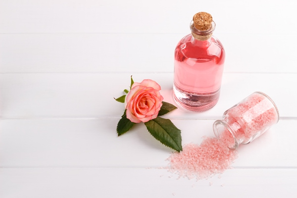 Bottle of rose absolute oil and rose flower on white surface