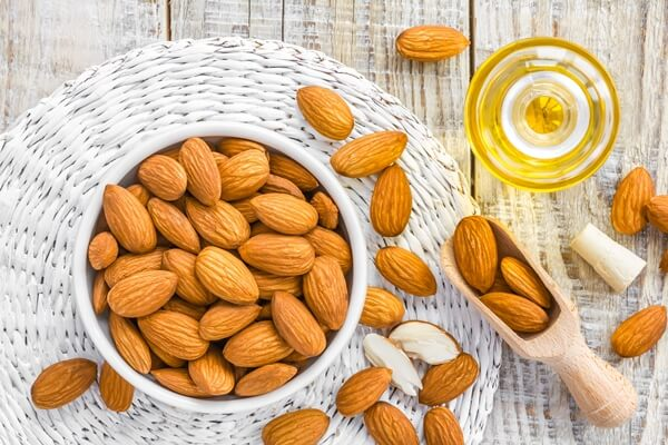 Almond nuts and a bottle of argan oil
