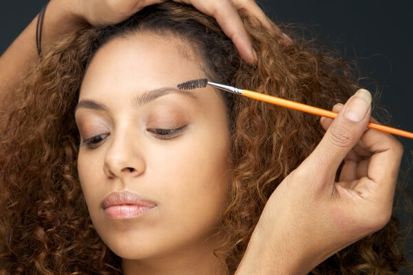 Pretty girl having her eyebrow applied with castor oil using a mascara wand