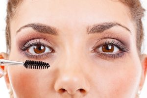 Close-up on woman's face while applying castor oil for eyelashes