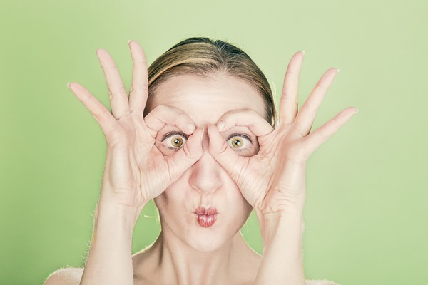 Woman making a funny face, her long eyelashes making her eyes stand out
