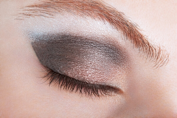 Close-up of a closed eye with dark grey eye shadow; eyelashes are long and thick