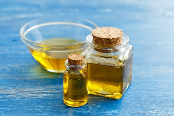Castor oil in bottles and in a transparent glass bowl