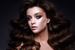 Brunette woman dolled up in smokey eye makeup and long wavy hair